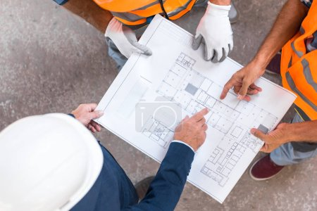 Photo for Top view of three men standing and pointing with fingers at blueprint - Royalty Free Image