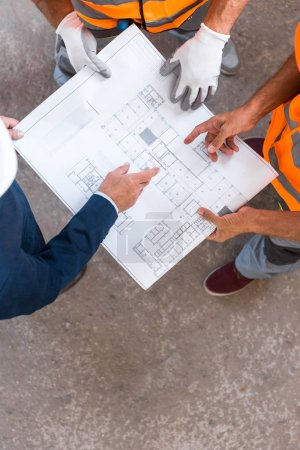Photo pour Vue recadrée des constructeurs et des hommes d'affaires debout et tenant le plan directeur - image libre de droit