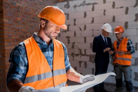 Photo pour Focalisation sélective du constructeur examen du plan près d'un collègue et d'un homme d'affaires - image libre de droit