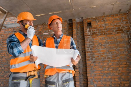 Photo for Constructor holding blueprint near handsome coworker with walkie talkie - Royalty Free Image