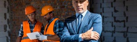 Photo pour Photo panoramique d'un homme d'affaires debout aux bras croisés près de constructeurs - image libre de droit