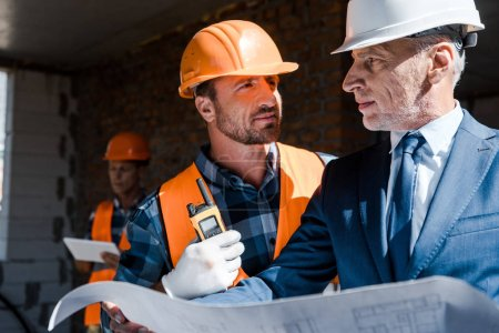 Photo for Selective focus of businessman holding blueprint near constructor - Royalty Free Image