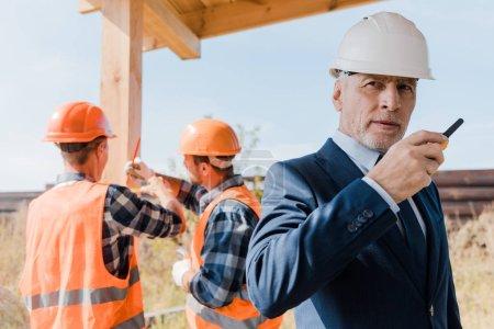 Photo pour Focus sélectif d'un homme d'affaires barbu d'âge moyen avec talkie walkie - image libre de droit