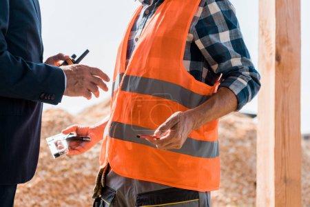 Photo pour Crochet vue d'un homme d'affaires tenant un talkie près d'un constructeur - image libre de droit