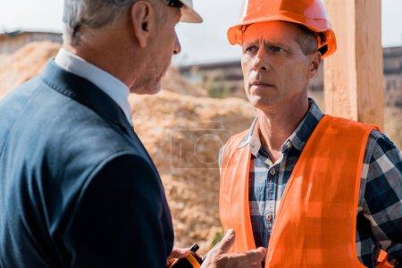 Photo pour Focalisation sélective d'un constructeur expérimenté regardant l'homme d'affaires - image libre de droit