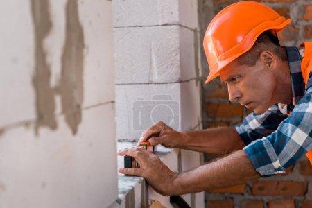 foyer sélectif du constructeur d'âge moyen dans le casque mesurant mur de béton