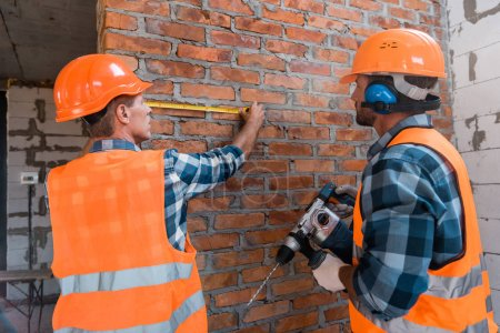Photo pour Constructor measuring brick wall near coworker with hammer drill - image libre de droit