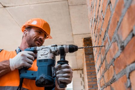 Photo for Handsome man in earphones holding hammer drill near brick wall - Royalty Free Image