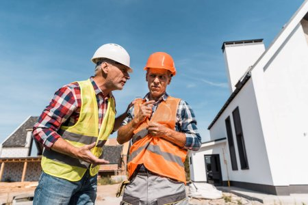 Photo for Middle aged constructors in helmets standing near houses - Royalty Free Image