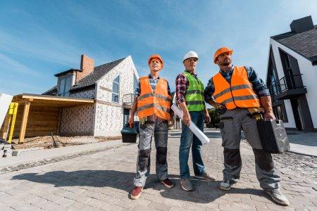 Photo pour Constructeurs de casques tenant des boîtes à outils près des maisons - image libre de droit