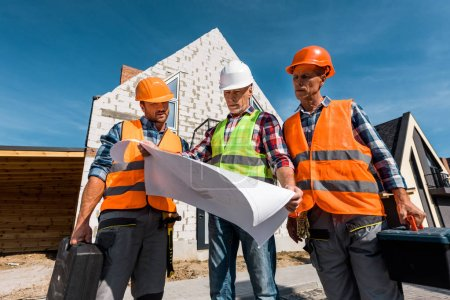 Photo for Constructors in helmets holding toolboxes and looking at blueprint near houses - Royalty Free Image