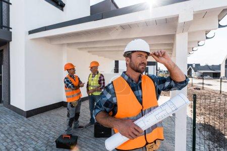 Photo pour Focalisation sélective du constructeur avec plan touchant le casque près des hommes - image libre de droit
