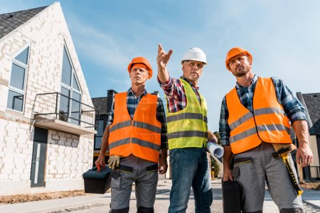 Photo pour Constructeurs de casques tenant des boîtes à outils près de collègues gesticulant près des maisons - image libre de droit