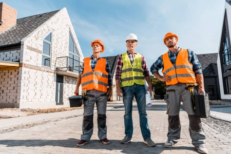 Photo for Middle aged constructors in helmets standing with coworker near houses - Royalty Free Image