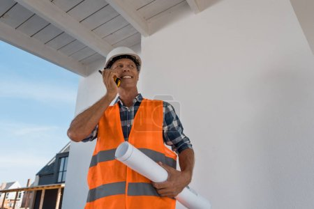 happy mature man holding walkie talkie and blueprint