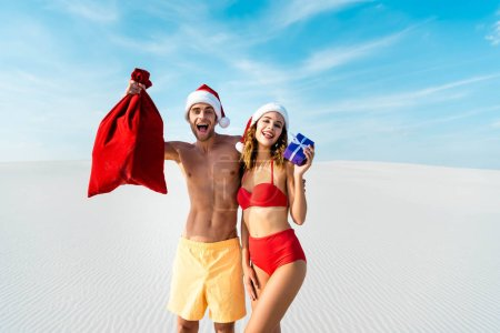 Photo pour Sexy and smiling girlfriend holding gift and boyfriend with santa sack on beach in Maldives - image libre de droit