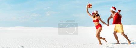 Photo pour Photo panoramique d'une copine sexy et souriante tenant un cadeau et un petit ami avec santa sack sur la plage aux Maldives - image libre de droit