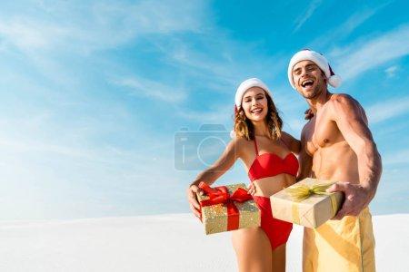 Photo pour Sexy et souriante amie et petit ami tenant des cadeaux sur la plage aux Maldives - image libre de droit