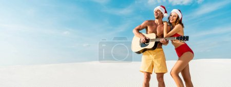 Photo pour Panoramic shot of sexy girlfriend and boyfriend playing acoustic guitar on beach in Maldives - image libre de droit