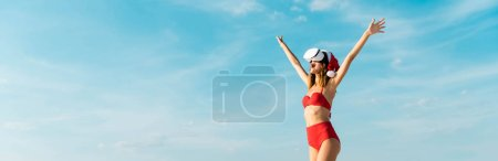 Photo for Panoramic shot of sexy woman in santa hat and swimsuit with virtual reality headset on beach in Maldives - Royalty Free Image