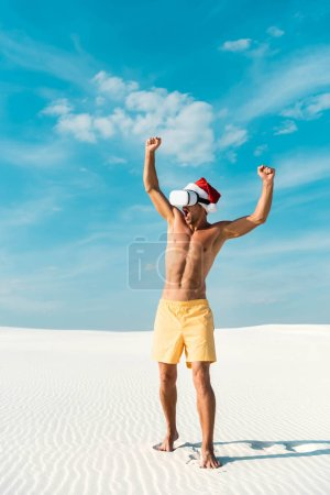 Photo for Sexy man in santa hat with virtual reality headset showing yes gesture on beach in Maldives - Royalty Free Image