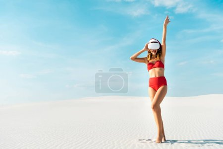 Photo pour Sexy woman in santa hat and swimsuit with virtual reality headset on beach in Maldives - image libre de droit