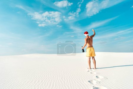 Foto de Back view of sexy man in santa hat holding glass and bottle on beach in Maldives - Imagen libre de derechos
