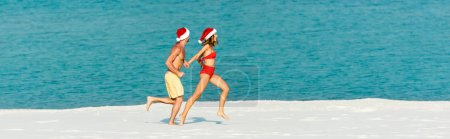 Photo for Panoramic shot of sexy girlfriend and boyfriend in santa hats running on beach in Maldives - Royalty Free Image
