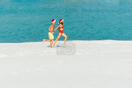 Photo for Sexy girlfriend and boyfriend in santa hats running on beach in Maldives - Royalty Free Image