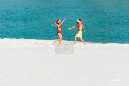 Photo pour Sexy girlfriend and boyfriend in santa hats with outstretched hands on beach in Maldives - image libre de droit