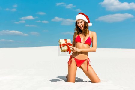 Photo for Sexy and smiling woman in santa hat and swimsuit holding christmas gift on beach in Maldives - Royalty Free Image