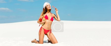 Foto de Panoramic shot of sexy and smiling woman in santa hat and swimsuit holding christmas gift and candy cane on beach in Maldives - Imagen libre de derechos