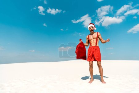 Photo for Shocked and sexy man in santa hat holding santa sack on beach in Maldives - Royalty Free Image