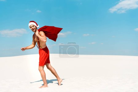 Photo pour Handsome and sexy man in santa hat holding santa sack and walking on beach in Maldives - image libre de droit
