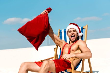 Photo for Handsome and sexy man in santa hat holding santa sack and sitting on deck chair on beach in Maldives - Royalty Free Image