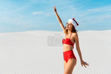 Photo pour Sexy and smiling woman in santa hat and swimsuit with outstretched hands on beach in Maldives - image libre de droit