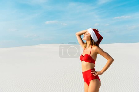 Photo pour Sexy and smiling woman in santa hat and swimsuit with closed eyes on beach in Maldives - image libre de droit
