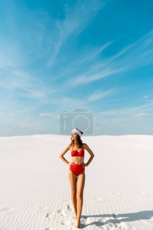 Photo for Sexy and smiling woman in santa hat and swimsuit with hands on hips on beach in Maldives - Royalty Free Image