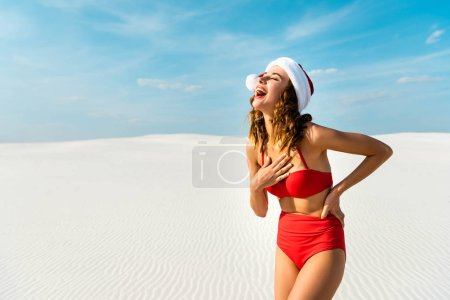 Photo pour Sexy and smiling woman in santa hat and swimsuit on beach in Maldives - image libre de droit