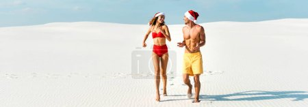 Photo pour Panoramic shot of sexy girlfriend and boyfriend in santa hats running on beach in Maldives - image libre de droit