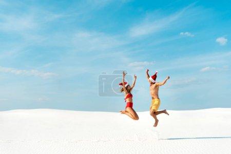 Photo pour Sexy girlfriend and boyfriend in santa hats jumping on beach in Maldives - image libre de droit