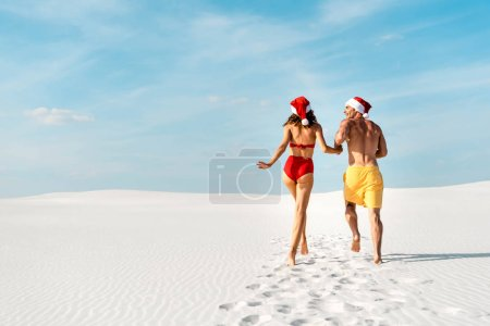 Photo pour Back view of sexy girlfriend and boyfriend in santa hats running on beach in Maldives - image libre de droit
