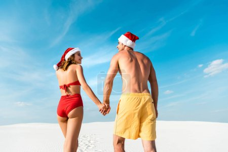 Photo pour Back view of sexy girlfriend and boyfriend in santa hats holding hands on beach in Maldives - image libre de droit