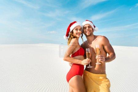 Photo pour Sexy petite amie et petit ami tenant des lunettes de champagne et serrant sur la plage aux Maldives - image libre de droit