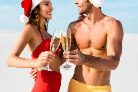 Photo for Selective focus of sexy girlfriend and boyfriend clinking with champagne glasses and hugging on beach in Maldives - Royalty Free Image