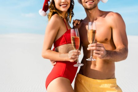 Photo pour Cropped view of sexy girlfriend and boyfriend holding champagne glasses and hugging on beach in Maldives - image libre de droit