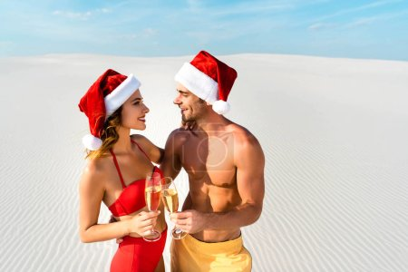 Photo for Sexy girlfriend and boyfriend clinking with champagne glasses and hugging on beach in Maldives - Royalty Free Image