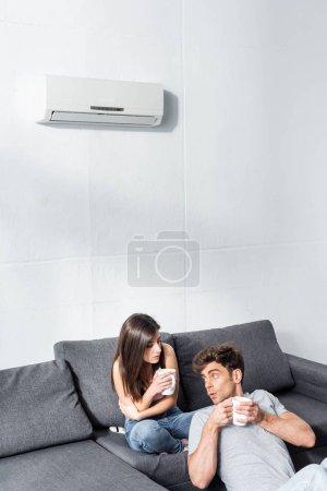 Photo pour Attrayant petite amie et beau petit ami tenant tasses avec thé - image libre de droit