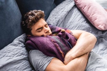 Photo pour Sick and handsome man in scarf with closed eyes lying in bed - image libre de droit