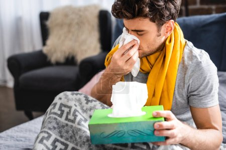 Photo pour Sick man in scarf sneezing and holding napkin in apartment - image libre de droit